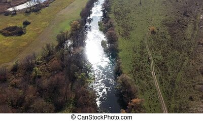 Shooting from above the famous and beautiful river Oskol in autumn sunny day in the Dvurechansky National Park in Kharkov region, Ukraine. Summer nature from above. Drone footage. Top view of trees.