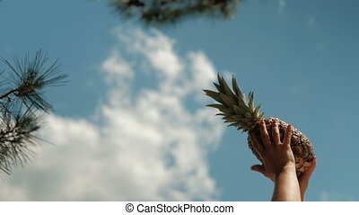 Shooting from bottom of girl hand raises pineapple up, rests...