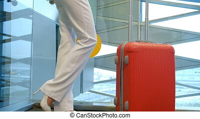 Shooting from down blonde woman standing, waving hand in airport