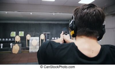 Shooting gallery. A concentrated young man aiming in a...