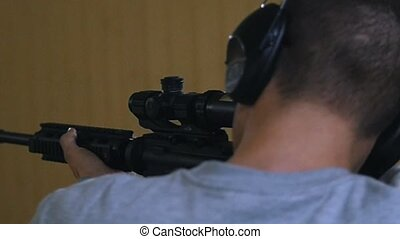 Shooting gallery. A young man aiming using a rifle. Close up