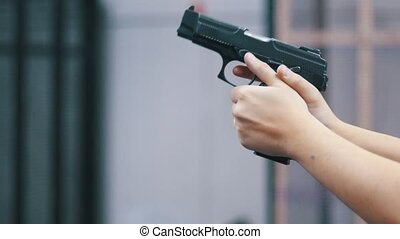 Shooting gallery. A young man holding a gun and shooting