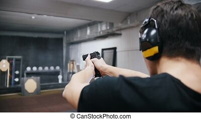Shooting gallery. A young man in black t-shirt shooting with...