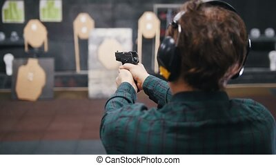 Shooting gallery. A young man shooting on a shooting range....