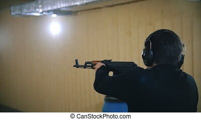 Shooting gallery. A young man shooting using a rifle. Slow...