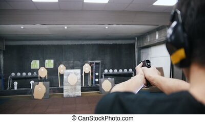 Shooting gallery. A young man shooting with a firearms....