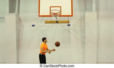 Shooting Hoops - Man practices shooting hoops at an indoor...