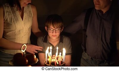 shooting in the dark. A teenage boy with glasses blows out candles on the cake.