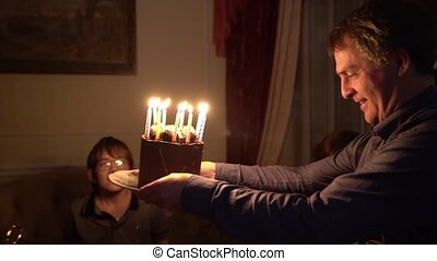 shooting in the dark. dad brought a cake with candles for his son.