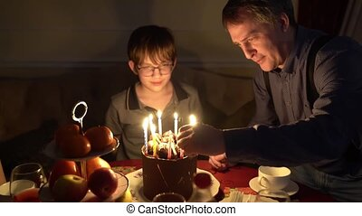 shooting in the dark. dad lights the candles on the cake.