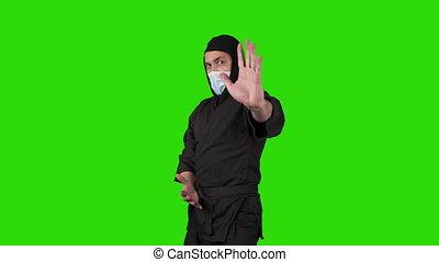 Shooting of man in black costume ninja on green background