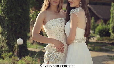 Shooting of two lovely girls in wedding dresses and tiaras for a fashion magazine outdoors in the park
