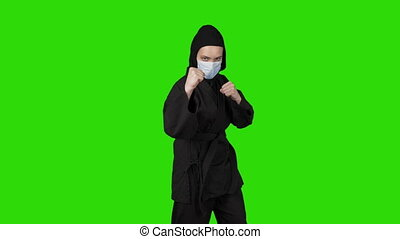 Video of woman in black costume ninja on green isolated background