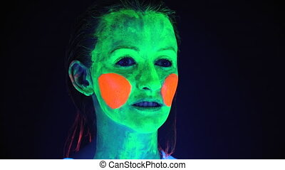 Video of woman with scary painted face in ultraviolet light