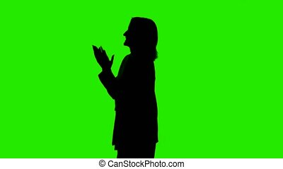 Shooting of woman's silhouette in suit jacket with applause on green background
