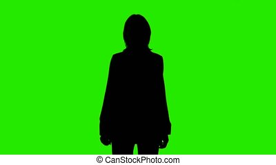 Shooting of woman's silhouette in suit jacket with thumb gesture on green