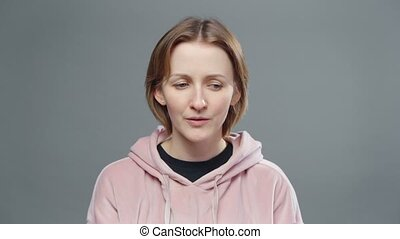 Video of young woman in pink sweatshirt on grey background
