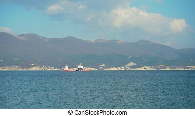 Shooting the movement of cargo ships in the open sea on the background of other ships, mountains, sea and sky.