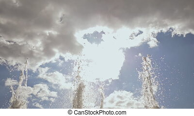 Shooting under the streams of a fountain in the form of a semicircle or a rainbow. Shooting in slow motion.