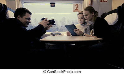 Shooting video of mom and child using pad during train ride...