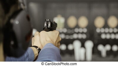 Shooting with a pistol. A closeup of a pistol in his hand....