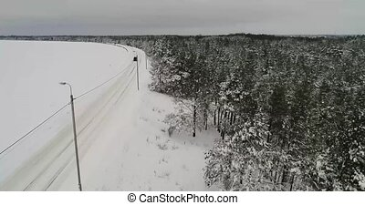 Shooting with air-road passing lengthwise snowy forest