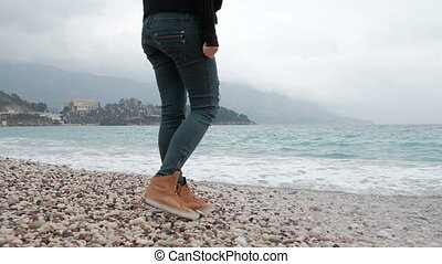 Shooting woman legs walking on sea shore close to blue water.