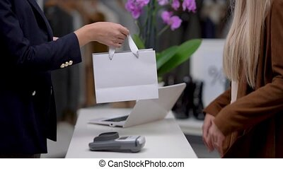 Shop assistant and customer in boutique buying clothes