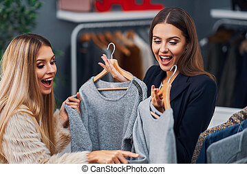 Shop assistant helping customer in boutique