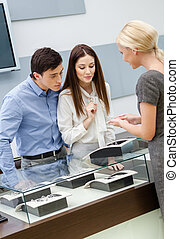 Shop assistant helps couple to select jewelry
