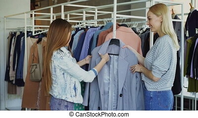 Shop assistant is helping young woman, bringing her coat and telling about model. Customer is touching it, comparing with other clothing while chatting with saleswoman