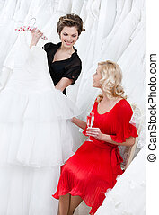 Shop assistant offers another dress to the bride