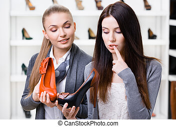 Shop assistant offers pumps for the customer - Shop ...