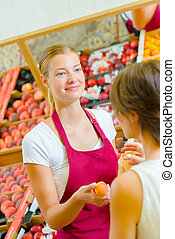 Shop assistant passing apricot to customer