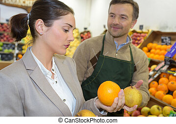 Shop assistant passing grapefruit to customer