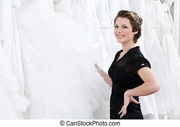 Shop assistant picks out the dress