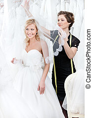 Shop assistant puts wedding veil on the head of the bride,...