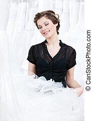 Shop assistant selects a proper dress for the client