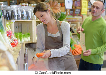 Shop assistant serving carrots to customer
