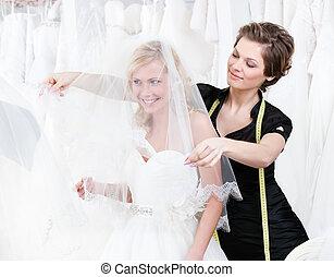 Shop assistant sets the veil of the bride