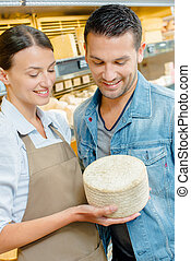 Shop assistant showing customer a whole cheese