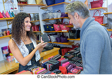 Shop assistant showing wallet to male customer