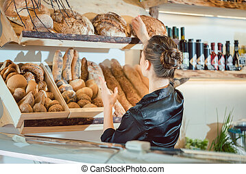 Shop assistant sorting bread to be sold