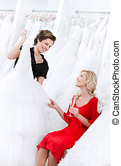 Shop assistant suggests another dress to the bride