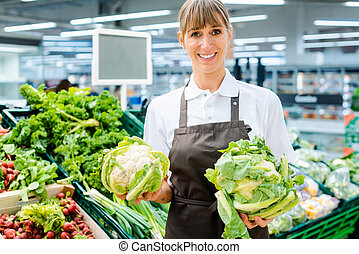 Shop assistant woman in supermarket showing the fresh produce