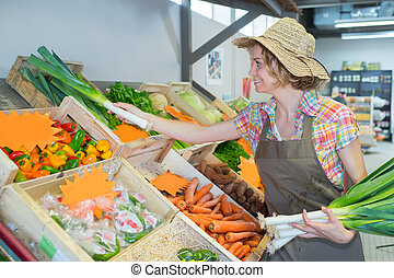shop assistant working at fruit department in supermarket