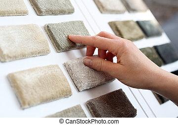 Shop carpets. - Woman in shop with carpets chooses carpet...