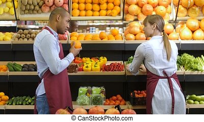 Shop clerk at grocery shelf checking products - Mixed race...