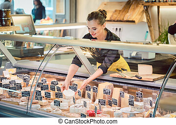 Shop clerk woman sorting cheese in the supermarket display