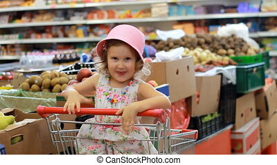 Shop discounts. Sale. Child girl in a supermarket sits in a shopping cart.